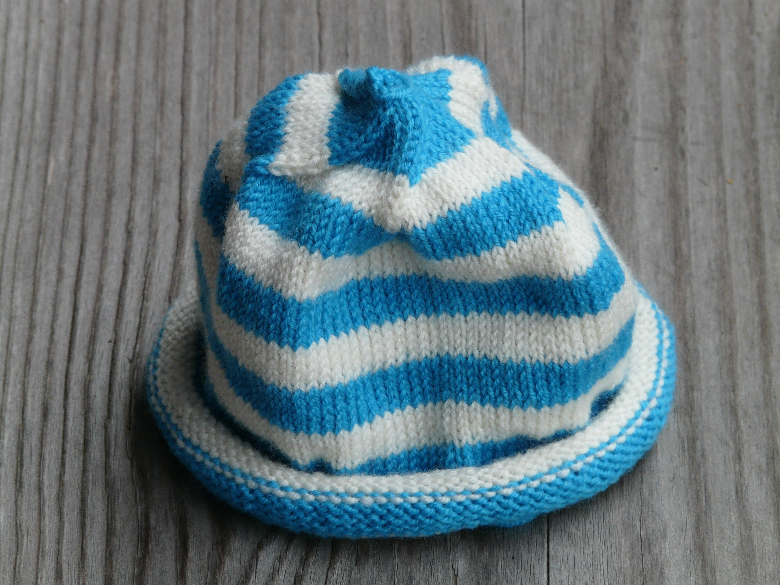 2172a4f3567 A blue and white striped bknitted baby hat representing charitable crafting  items